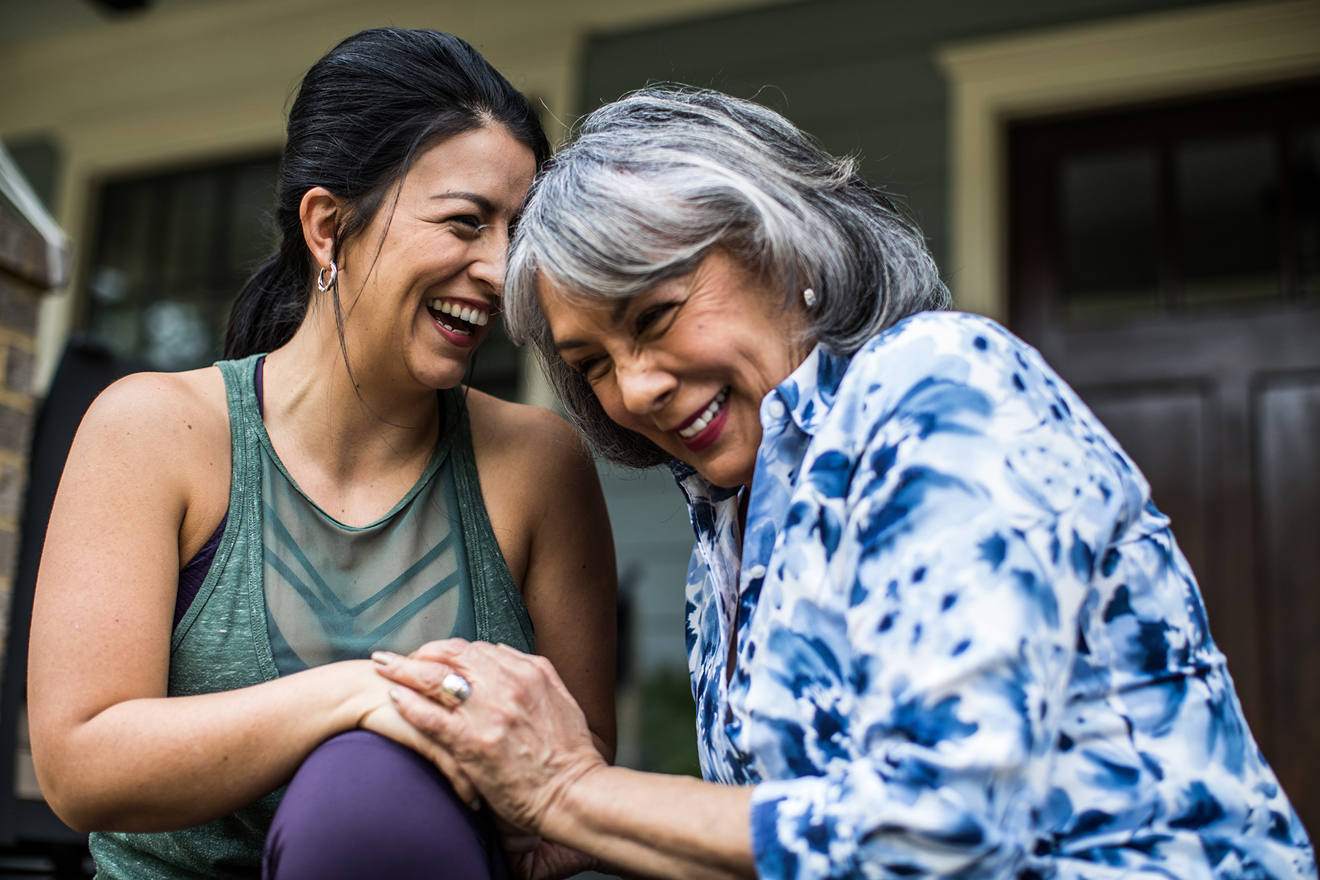 mother daughter laughing and holding hands on porch