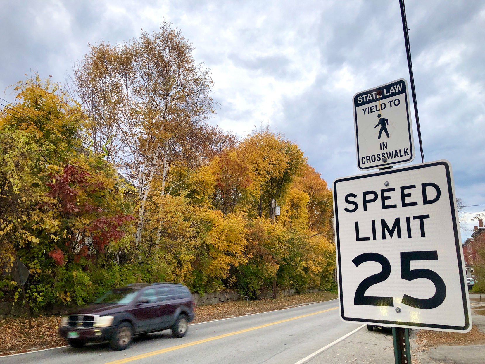 Car driving down a street in Rumford, Maine with speed limit sign
