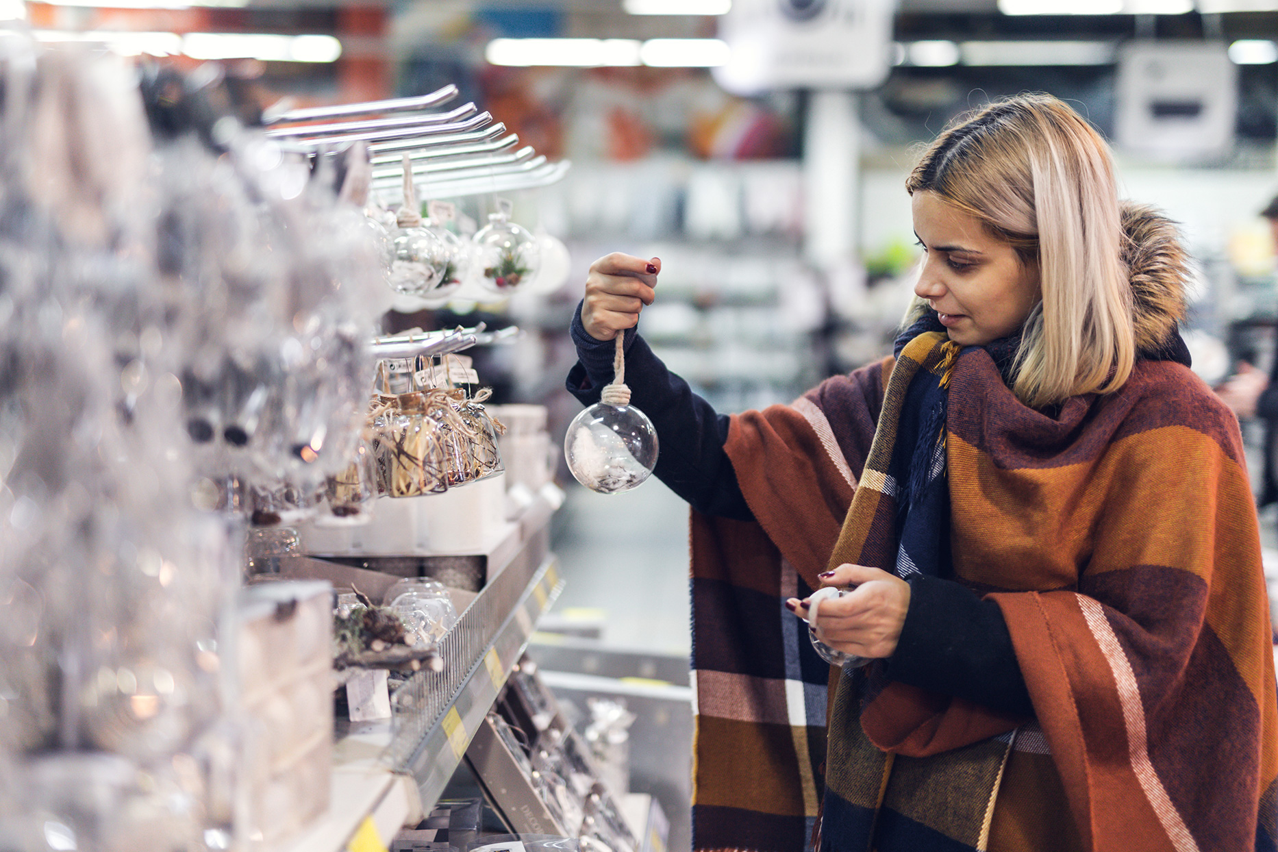 woman holding up christmas ornament while shopping for christmas decor