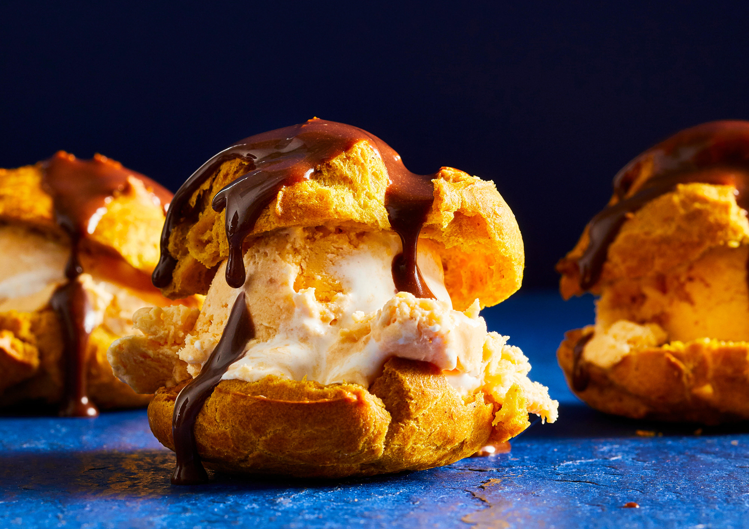 side view of Cream Puffs filled with Pumpkin Ice Cream and chocolate drizzle