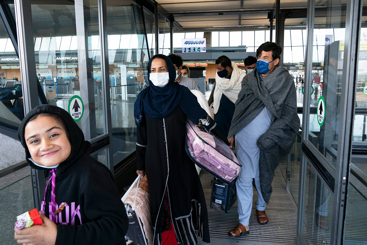 Families evacuated from Kabul, Afghanistan, walk through the terminal before boarding a bus after they arrived at Washington Dulles International Airport, in Chantilly, Va., on Wednesday, Aug. 25, 2021.