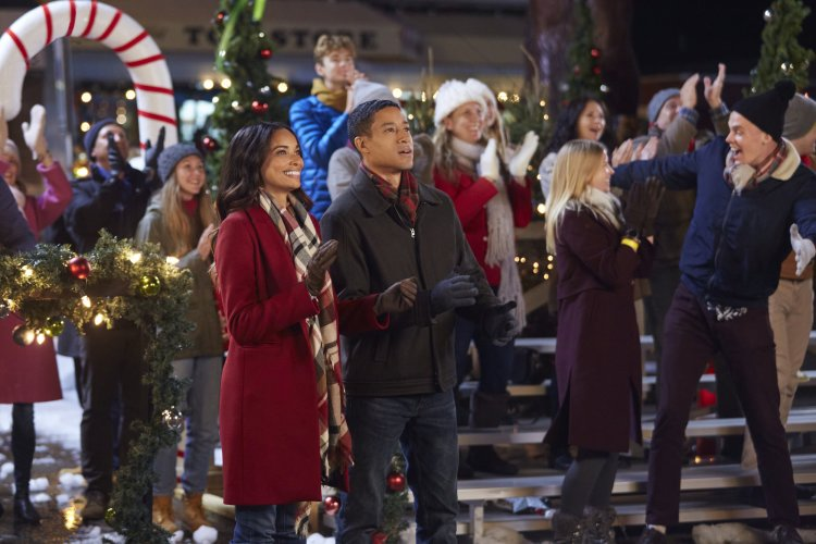 two people wearing coats at an outdoor christmas event
