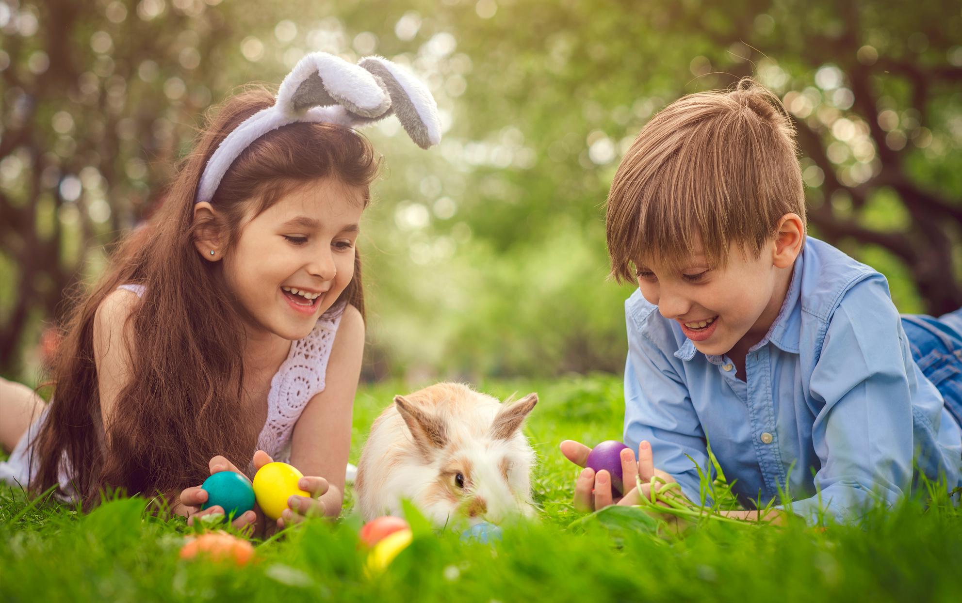 Two kids playing in the grass with an Easter bunny