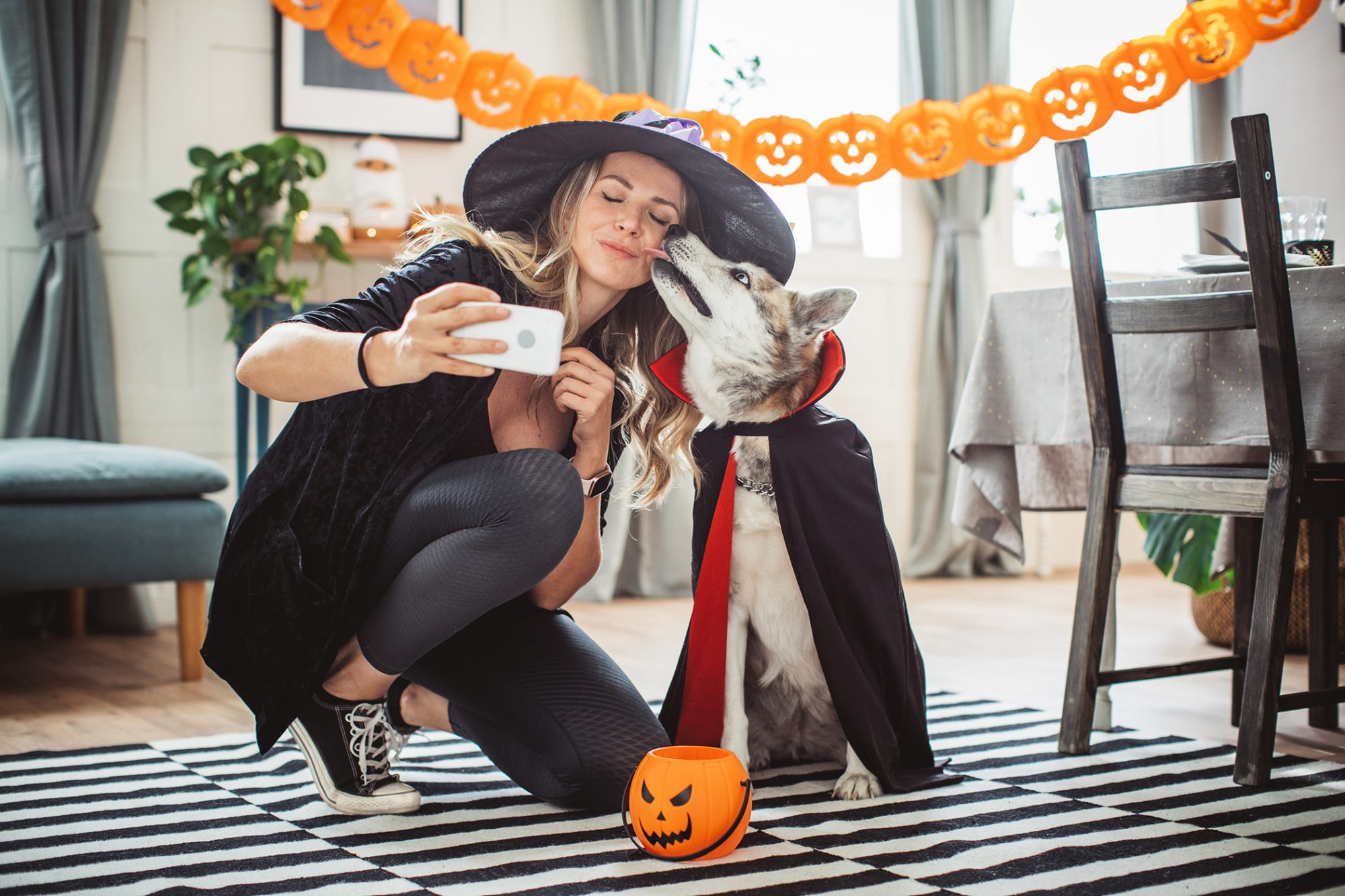 woman taking selfie with dog in costume