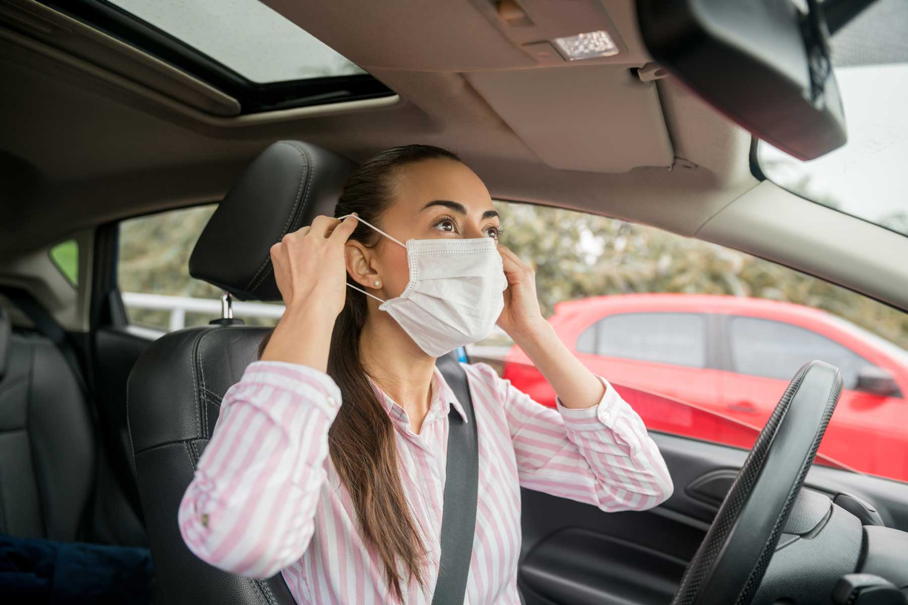 Woman putting on a facemask while in a car
