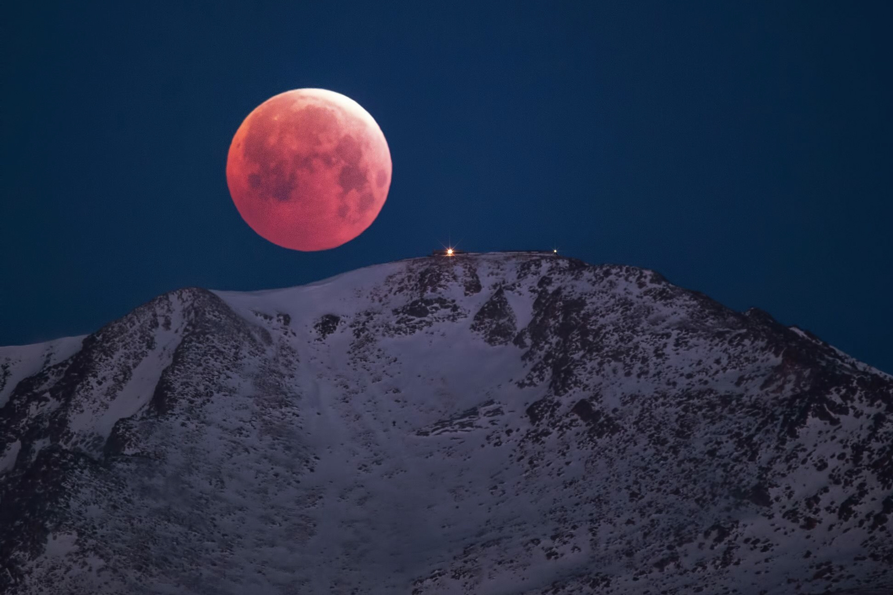 Scenic view of snowcapped mountain against sky at night with large full moon