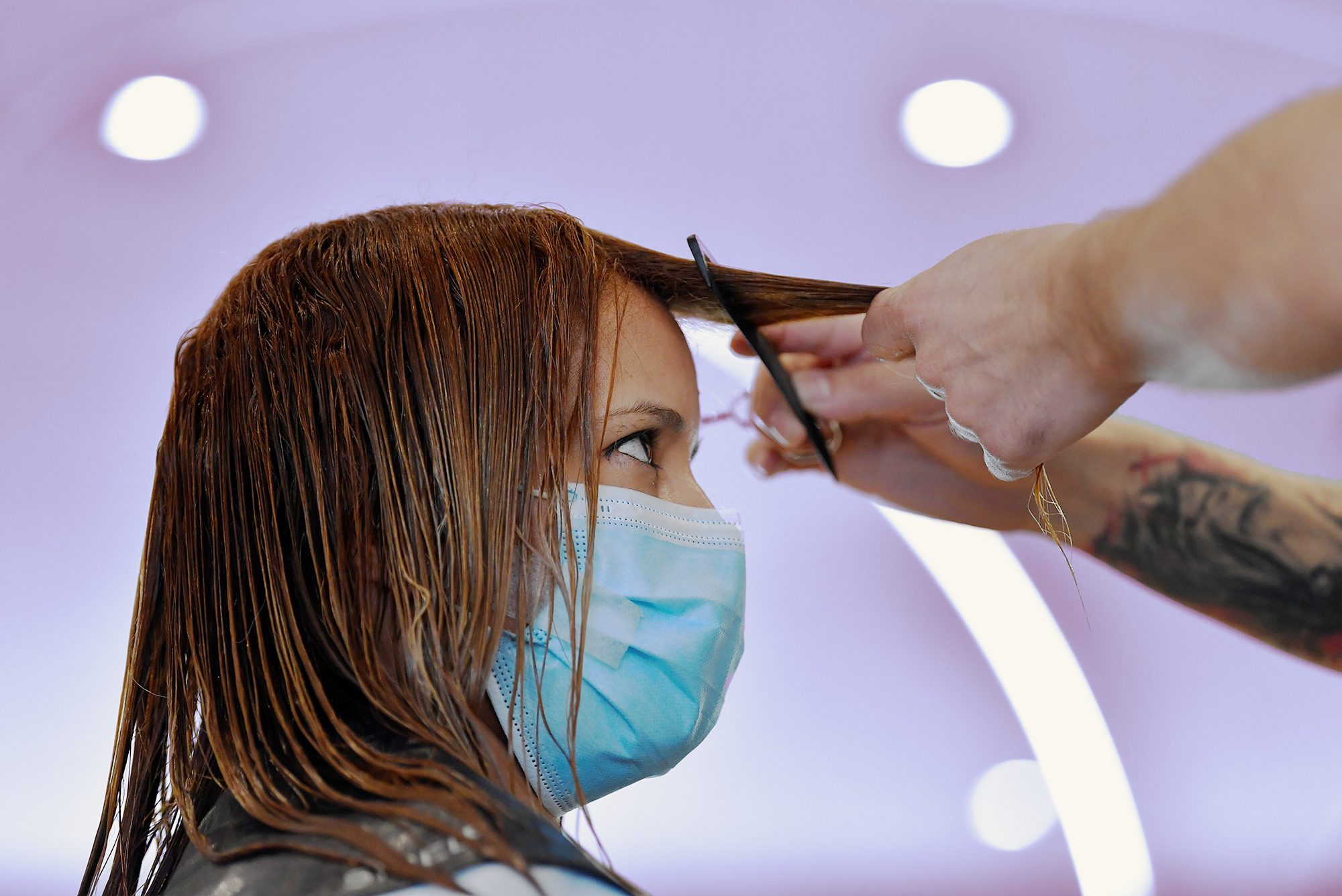 """A woman gets a haircut at the """"Hair & Look"""" salon, on May 18, 2020 in Ixelles, as Belgium eases lockdown measures taken to curb the spread of the COVID-19 pandemic, caused by the novel coronavirus. (Photo by JOHN THYS / AFP) (Photo by JOHN THYS/AFP via Getty Images)"""