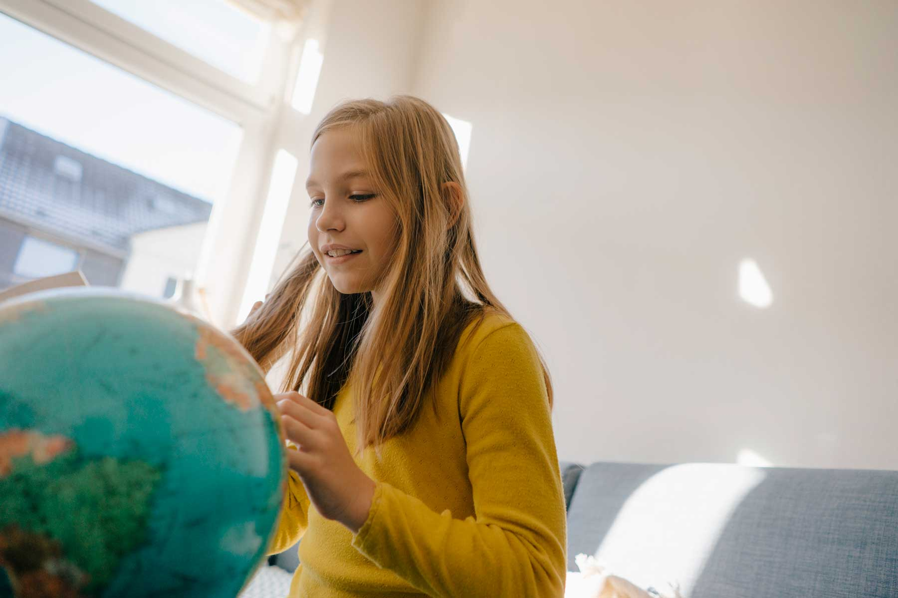 Girl at home looking at a globe