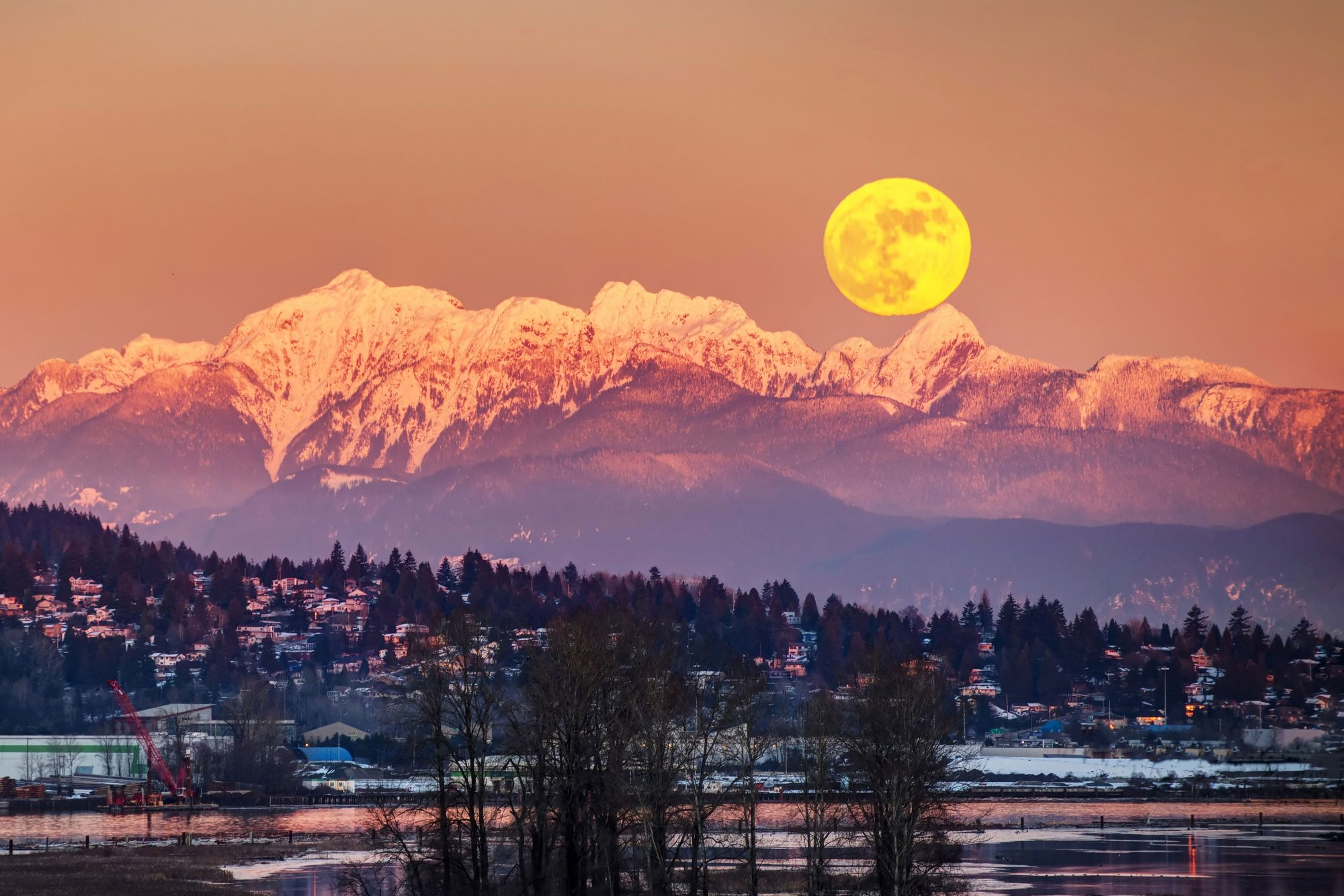 full moon rising over snow capped mountains
