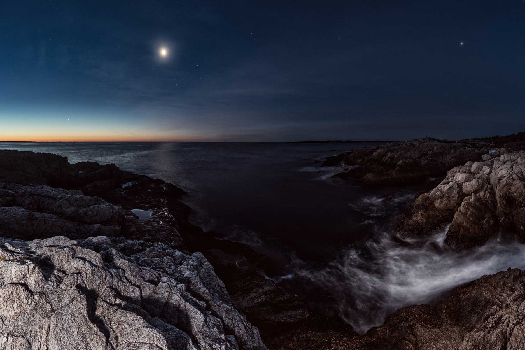 Mercury, Venus, Saturn, Mars, Jupiter, our Moon and Earth together in pre-dawn light overlooking a rugged stretch of Nova Scotian coastline. Long exposure with light painting.