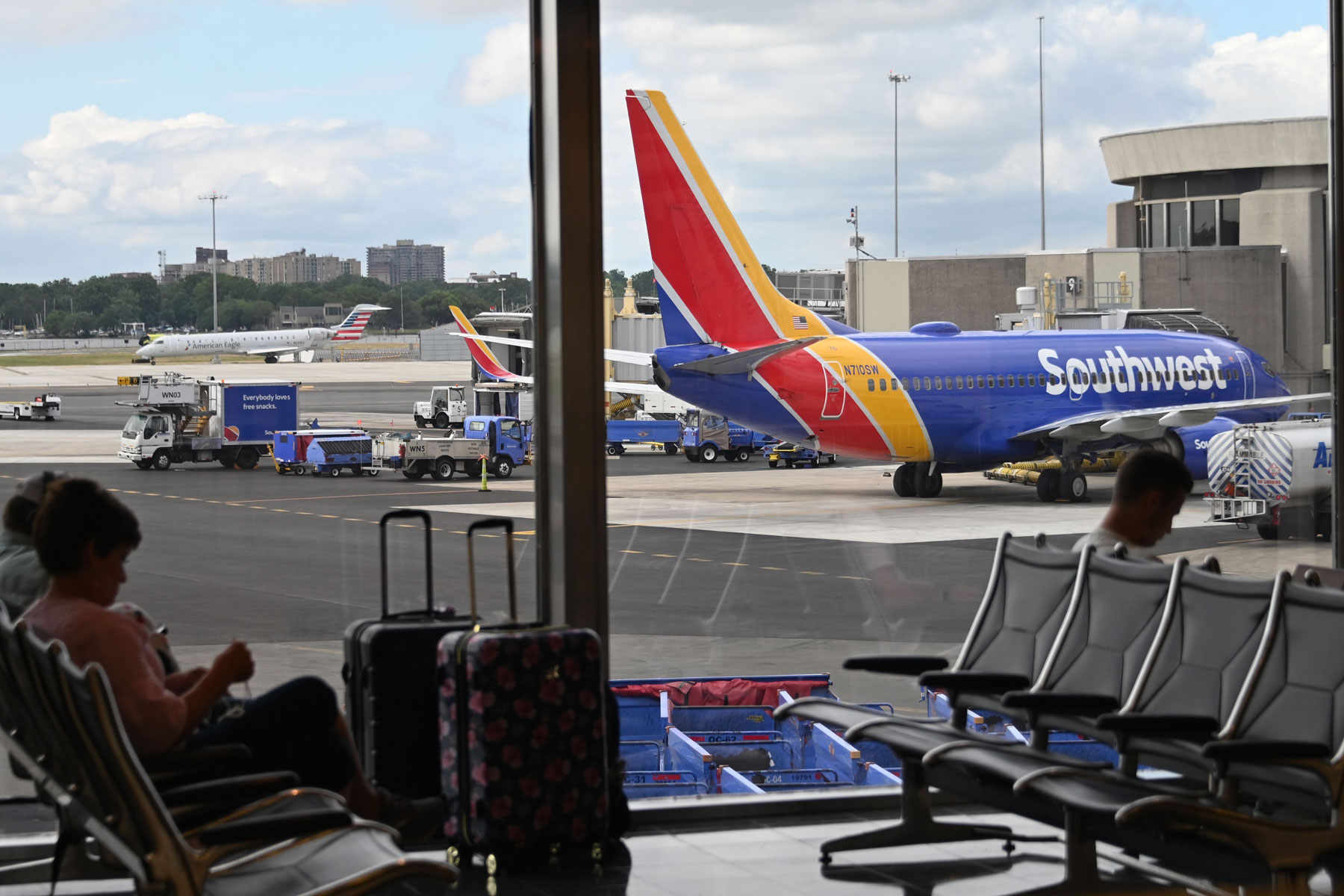 passengers waiting inside the airport have a view of a Southwest Airlines plane