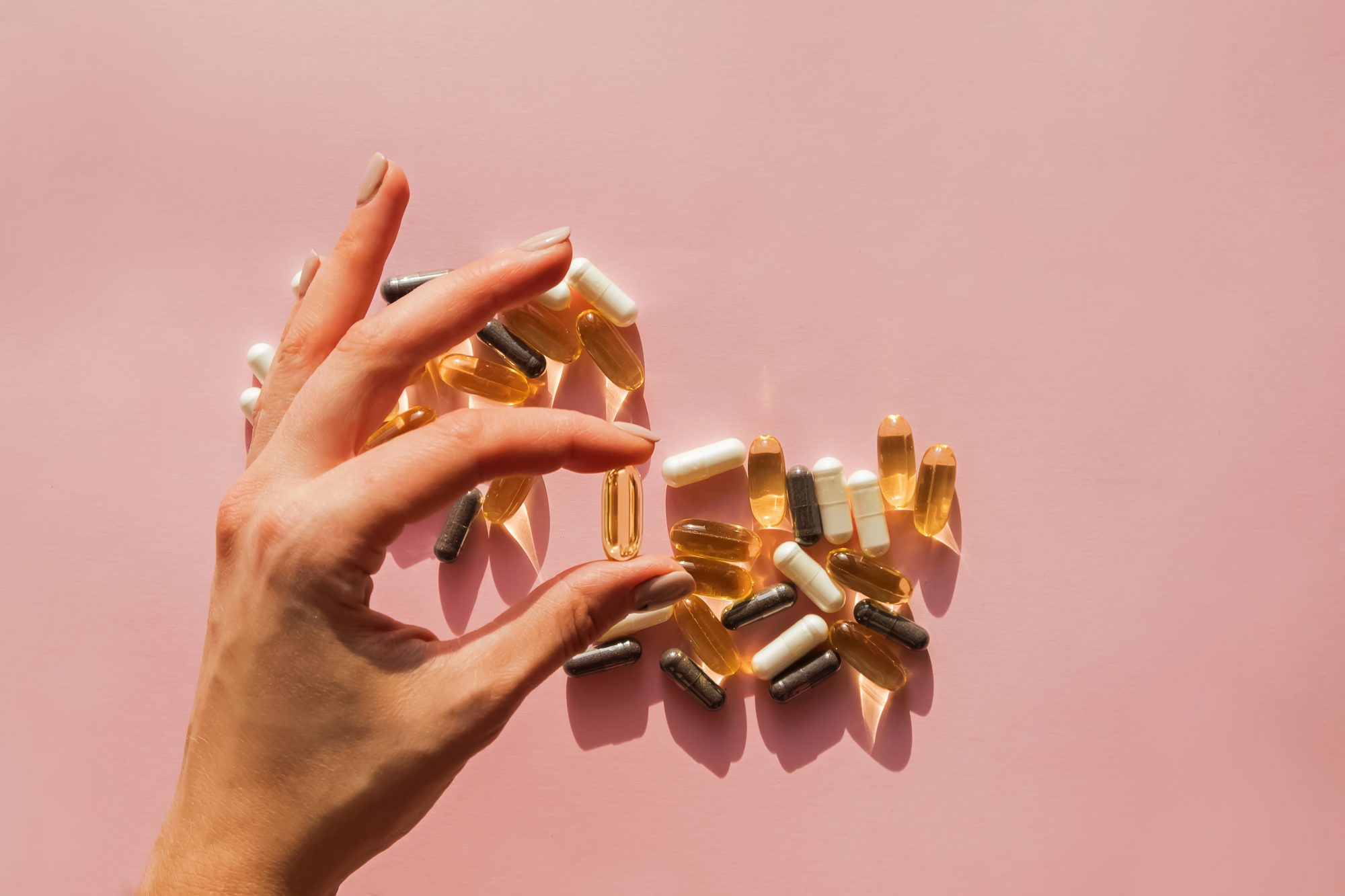 Immune Booster in the Age of Covid , Woman's hand holding a pill or dietic supplement capsule