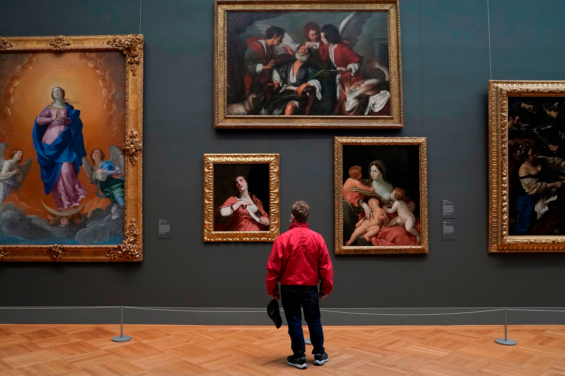 A patron looks at paintings on display