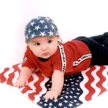 Baby With Star Cap Laying On Flag Blanket