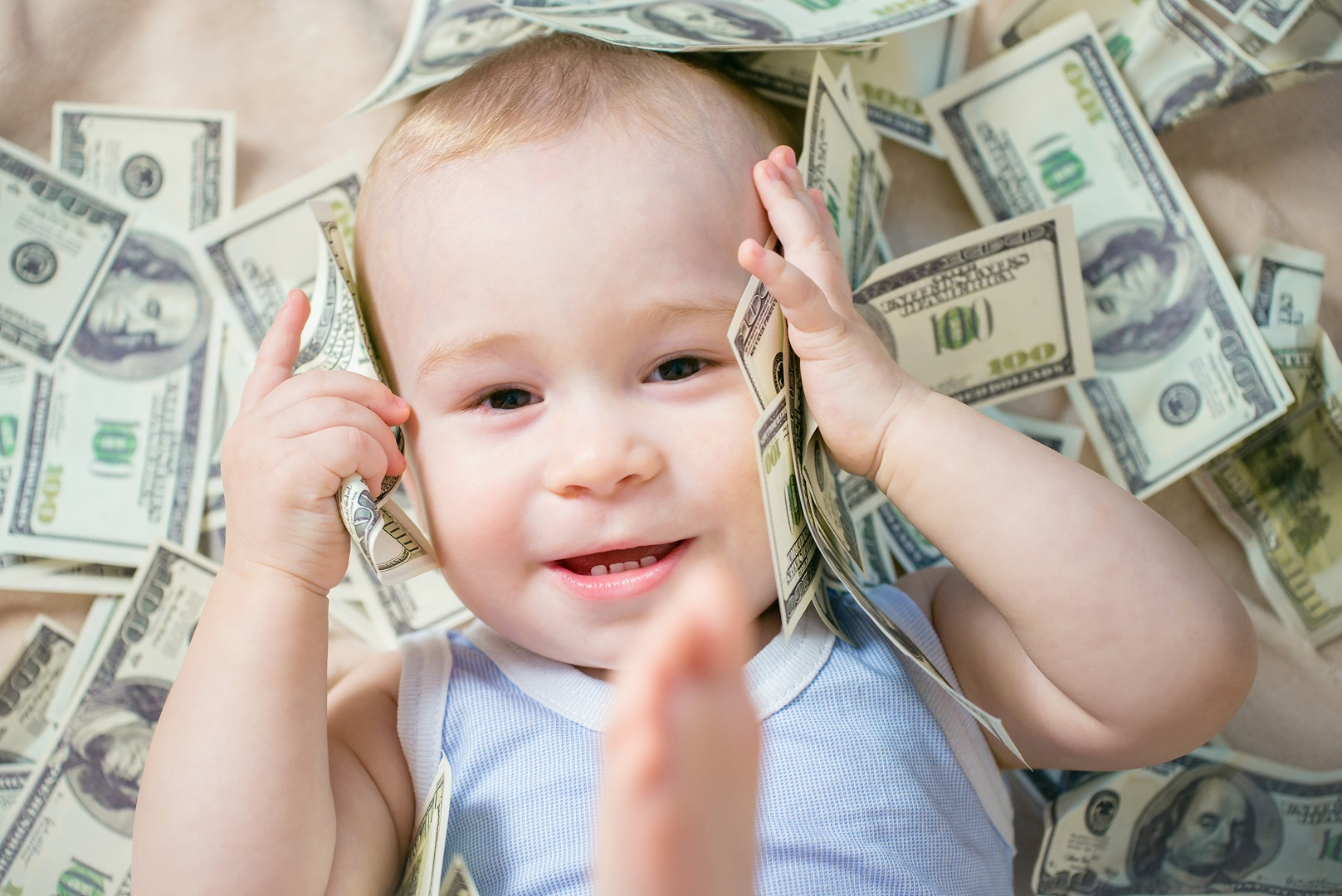 Baby Laying In Pile Of Money Holding Bills To Ears