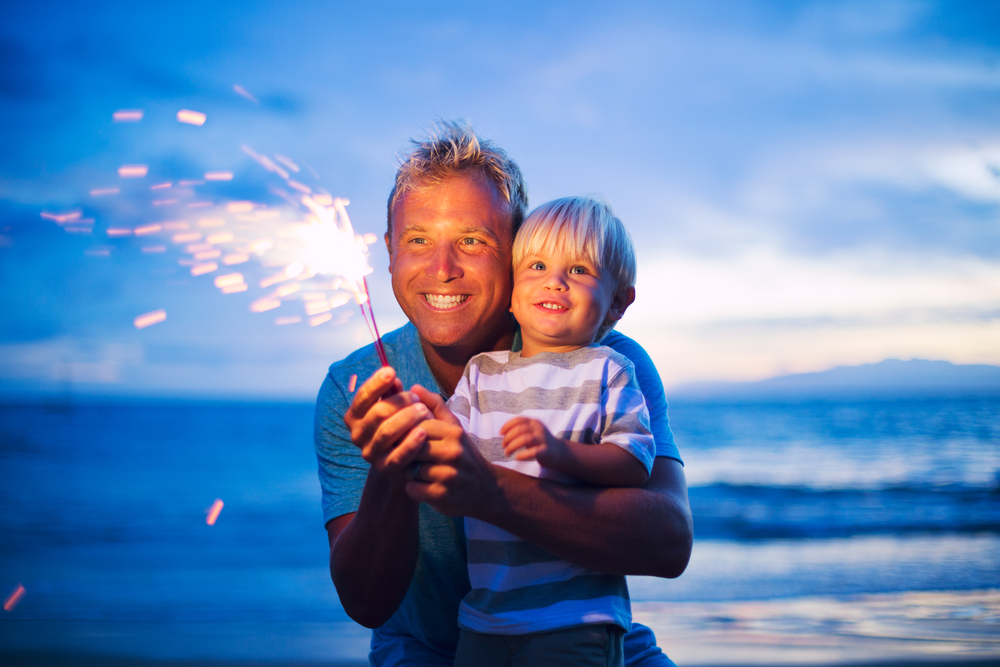 Father and son lighting sparklers