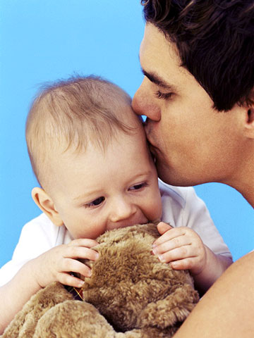 Wavy haired dad kissing baby in his arms, baby nibbling on bear