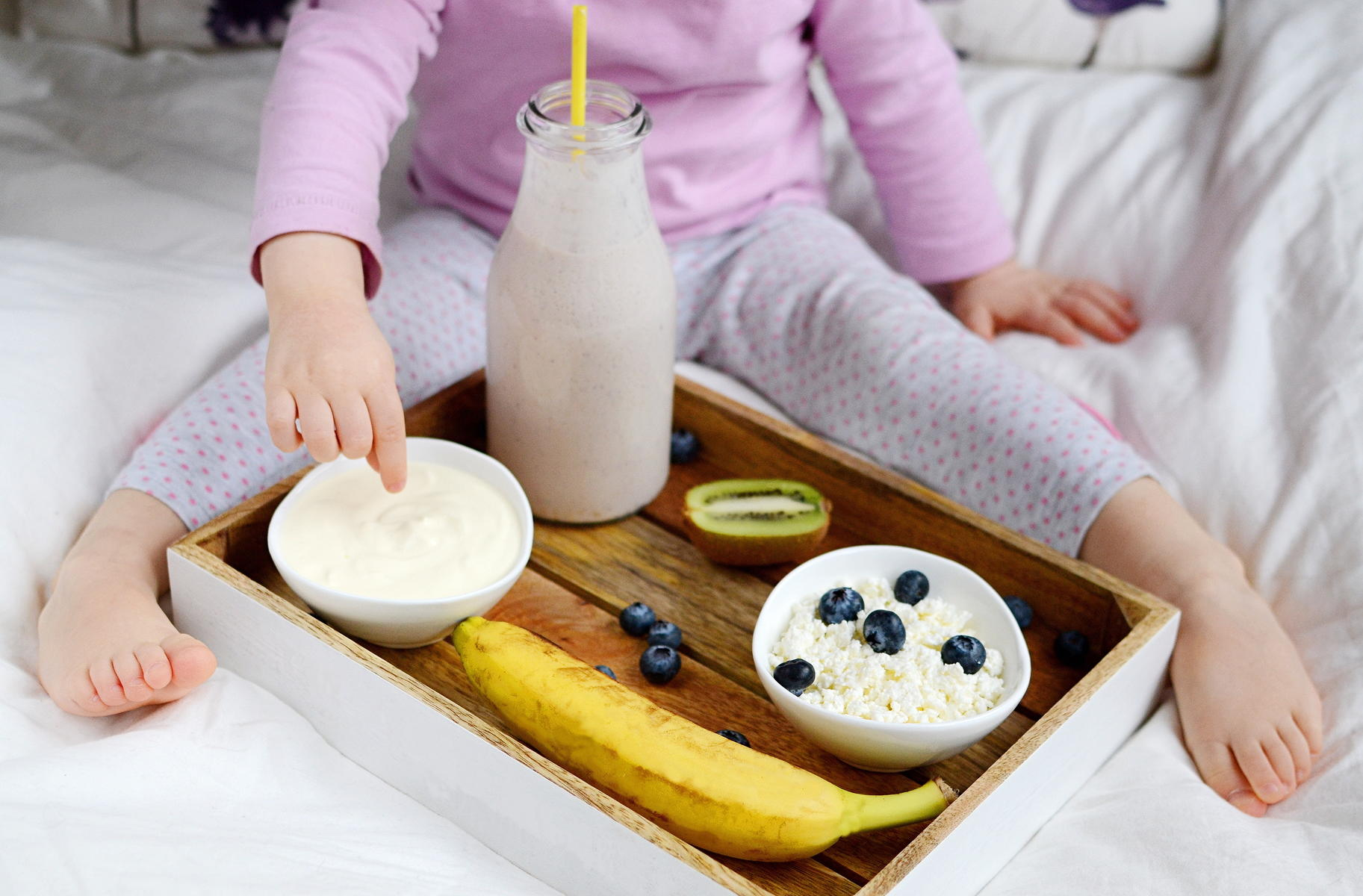 Little Girl Eating Healthy Breakfast In Bed