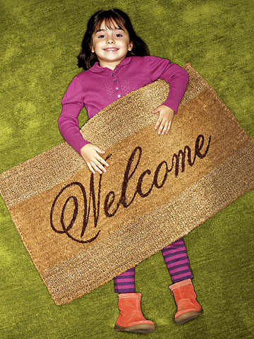 girl lying on floor with welcome mat on top of her