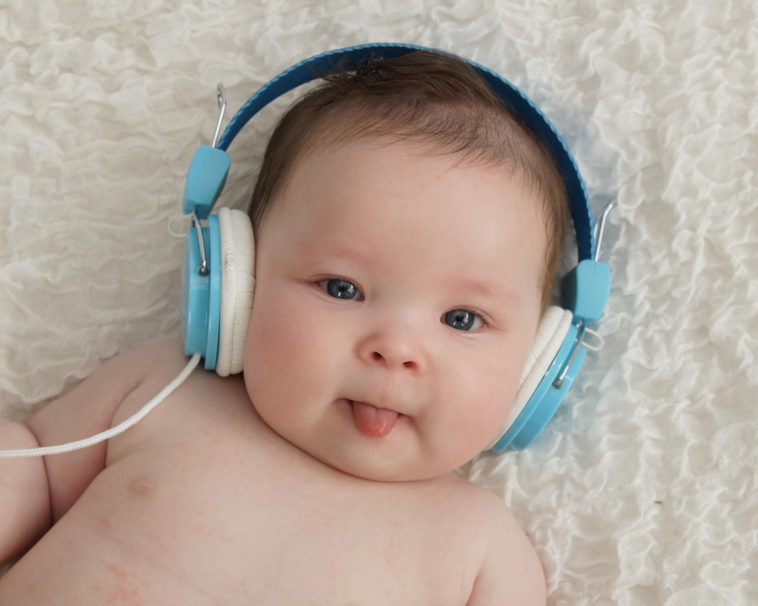 newborn with blue headphones