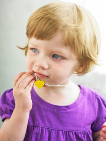 Girl biting on necklace