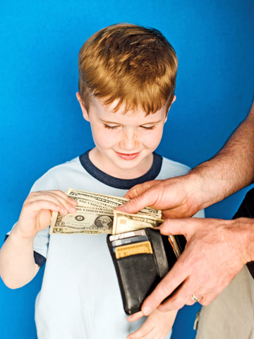 young boy holding wallet taking out cash