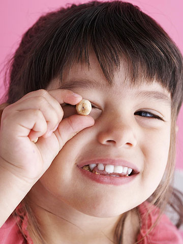 girl holding cheerio