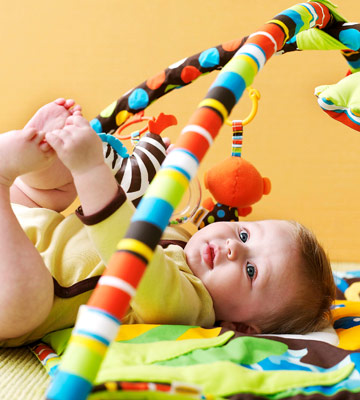 baby playing under Lil' Lion's Happy Hangout Activity Gym from Infantino