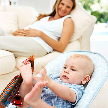baby in bouncy seat with mother watching