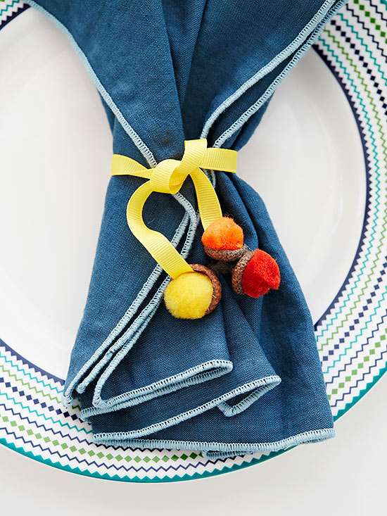 Pom-pom acorns on ribbons wrapped around fabric napkin