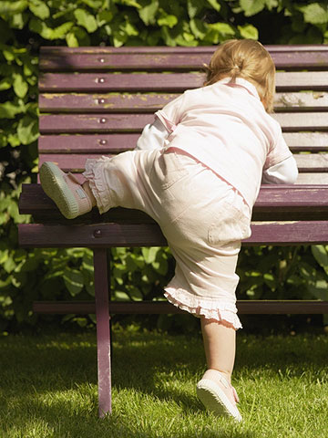 toddler climbing on park bench
