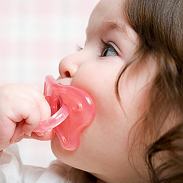 Baby girl sucking on pacifier