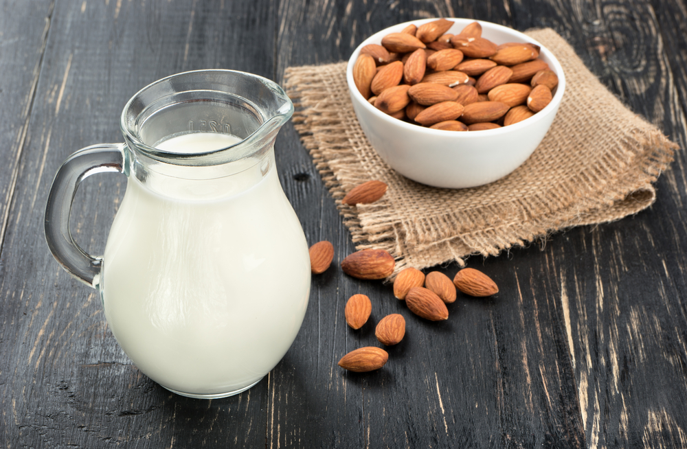 almond milk pitcher with bowl of almonds