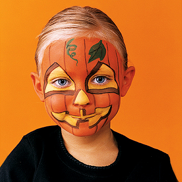 Child with face painted like a jack-o-lantern