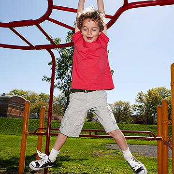 child hanging onto monkey bars