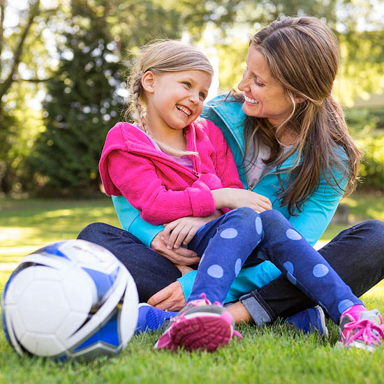 Mom and daughter sitting in grass with soccer ball