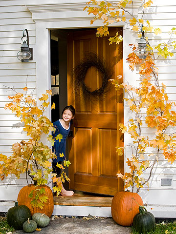 Girl opening door with pumpkins outside