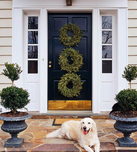 three wreaths on front door and pooch