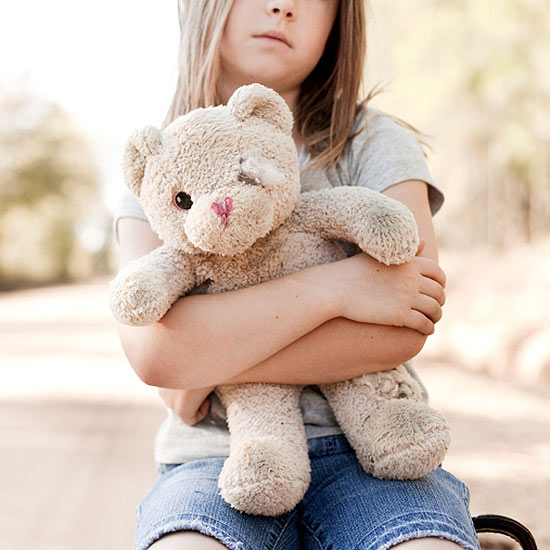 sad child holding teddy bear