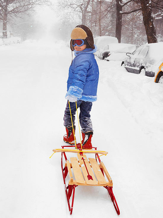 Girl pulling sled down snowy street