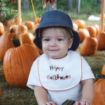 Toddler In Halloween Bib Standing In Pumpkin Patch