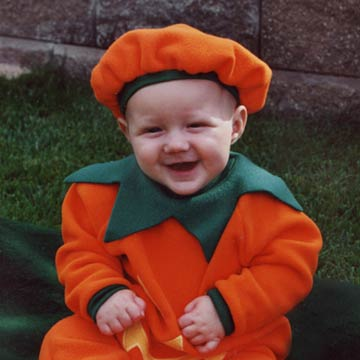 Baby Dressed In Pumpkin Costume Against Rocks