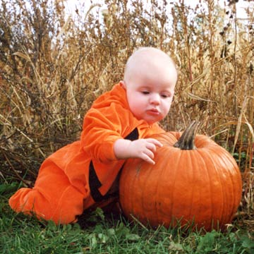 Baby In Pumpkin Costume Leaning On Pumpkin