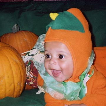 Baby In Pumpkin Outfit With Scarecrow Around Neck