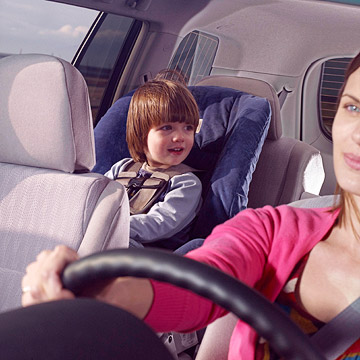 mother driving and daughter in car seat