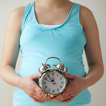 Pregnant woman holding clock