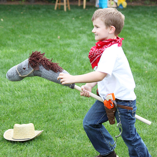Owen wearing cowboy costume and riding homemade horse