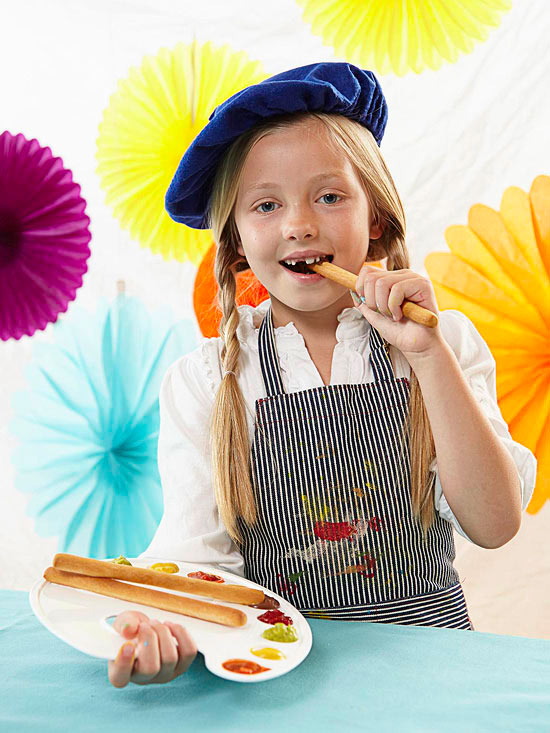 Girl artist eating breadstick and holding palette