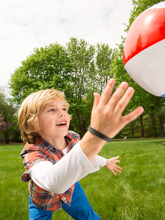 Boy reaching up at beach ball