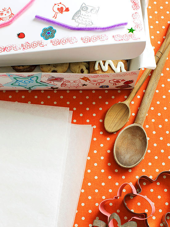 Table layout with cookie box at top, wooden spoons, and cookie cutters